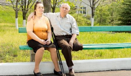 Dulce pareja hablar y sentarse en el banco del parque