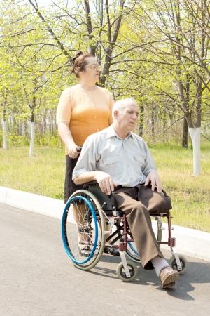 Mujer que empuja al hombre mayor en silla de ruedas en el parque
