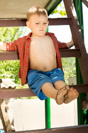 Young cute child sitting on a wooden swing in the park photo