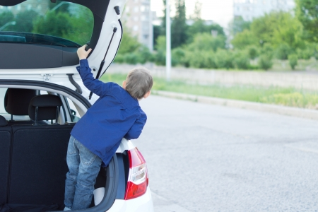 Young child seen from back standing in the open trunk of a car looking out to the front Stock Photo