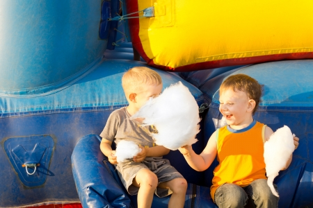 Happy young boys laughing sharing a large cotton-candy ball sitting near a colorful inflatable bouncer amusement 版權商用圖片
