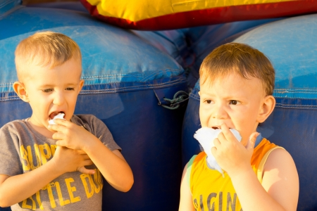 vivacious: Portrait of two young boys sharing a cotton-candy ball sitting near a colorful inflatable bouncer amusement