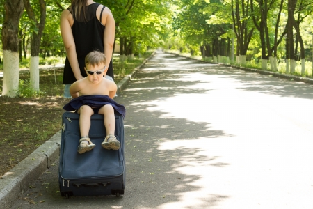transported: Close-up of a young boy being transported sitting on top of a trolley travel bag by the mother