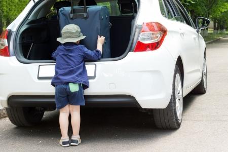 Ni�o peque�o empaque su equipaje en la parte trasera abierta de un auto hatchback, mientras se prepara para salir de vacaciones