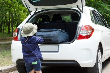 Small boy loading his suitcase into the open back of a hatchback car as he prepares to leave on holiday