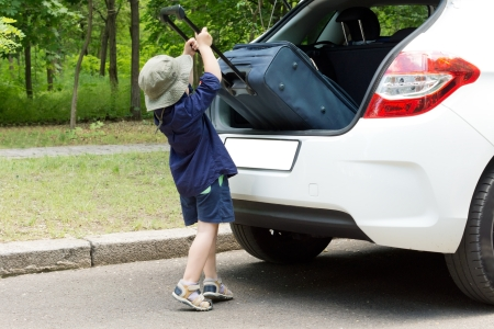 Cute little boy loading his case into the open back of a hatchback car reaching up on tiptoe as he tips it in Reklamní fotografie