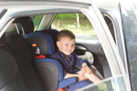 child seat: View through the open window of a car of a happy little boy strapped into a child seat