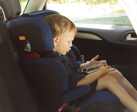 Little boy amusing himself in a car playing a game while strapped into his child safety seat waiting