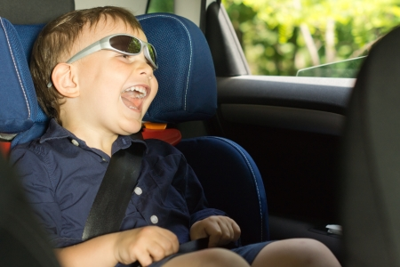 clowning: Happy little boy clowning around laughing as he sits in his child seat in the back of the car wearing trendy modern sunglasses