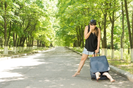 consternation: Mother looking in consternation at her son in a suitcase as she stands barefoot at the side of a leafy rural road and realises that he is hiding inside with his legs protruding Stock Photo