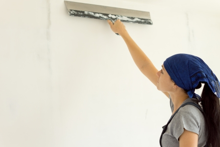 Woman applying wallpaper to a wall making sure that all the air bubbles have been eliminated while doing home renovations photo