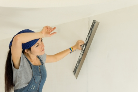 Tired woman wallpapering a wall pausing for a breather to wipe her forehead with her hand when doing home renovations photo