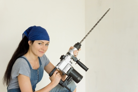 Young DIY woman holding an electric drill with a long bit photo