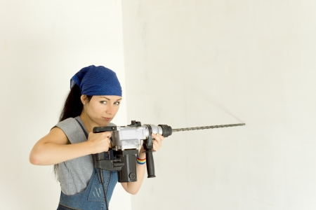 power operated: Competent woman with a battery operated cordless drill with a large masonry bit for drilling into a wall
