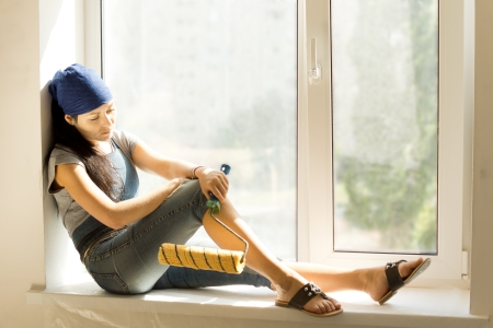 DIY woman taking a rest from decorating sitting on a window sill. photo