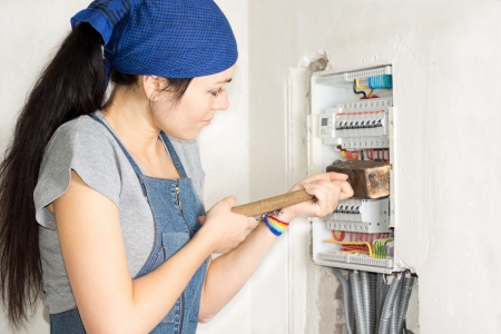 expedient: Housewife armed with a wooden mallet attacking an open electrical fuse box in frustration as she tries to solve her problems