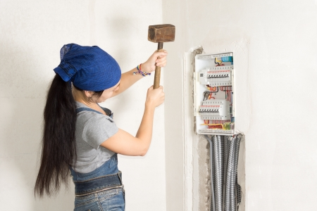expedient: Frustrated woman hitting an open electrical box taking aim at the circuit breakers as she seeks a solution to her problem