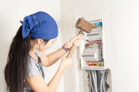expedient: Woman taking aim at an electrical fuse box with a large wooden mallet in an effort to solve her supply problems