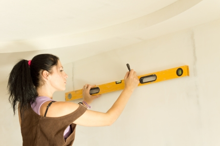 DIY young attractive woman using spirit level to work out measurements. photo