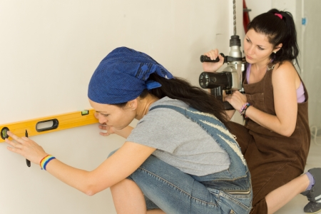 Two women doing home renovations working as a team with one marking the wall with the aid of a spirit level as the second waits with a masonry drill in her hands photo