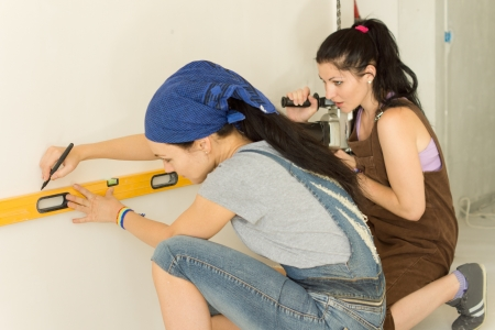 Two female friends doing DIY at home working as a team with one marking the wall with a spirit level while the second handles the electric drill photo