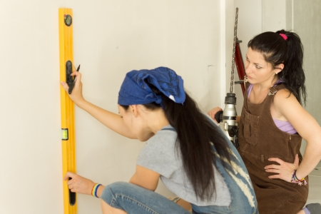 power operated: Woman marking a vertical line on a wall using a masons spirit level watched by her friend who is holding a large cordless drill