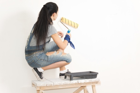 crouched: Young woman painting a wall with a roller balanced on a trestle or wooden table for extra height Stock Photo