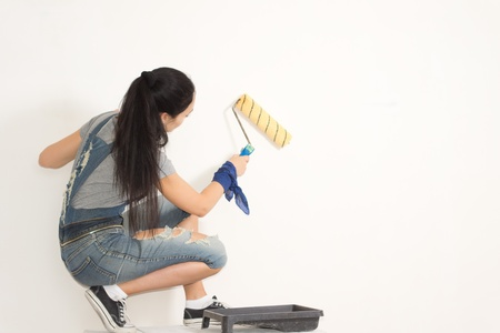 redecorating: Young woman redecorating her house painting a wall with a roller