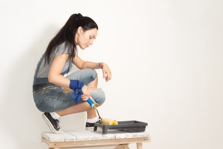 redecorating: Woman using a roller to paint a wall while renovating or redecorating her house taking paint from a plastic tray