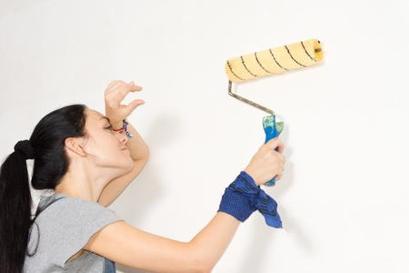 redecorating: Woman wiping her forehead with the back of her hand as she paints a wall with a roller while redecorating her house
