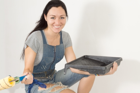 Closeup portrait of a young smiling happy woman with painting equipment redecorating her home photo