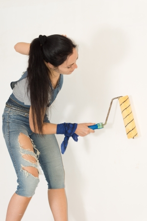 redecorating: Trendy young woman in ragged jeans standing painting a wall with a roller while redecorating Stock Photo