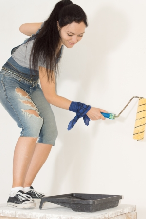 Smiling young housewife bending down painting an interior wall of her house with a roller photo