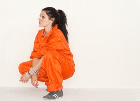squatting down: Woman in bright orange overalls squatting down facing left watching something off frame