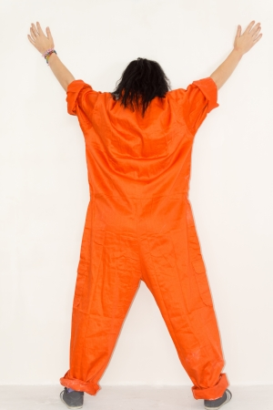 Woman standing with her back to the camera with her legs and arms outstretched displaying her huge outsized orange overalls photo