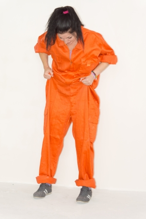 woman prison: Woman in outsized orange overalls standing looking down at her feet while pulling the pants up with her hands