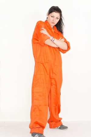 inmate: Attractive young woman posing in outsized bright orange overalls standing with her arms crossed