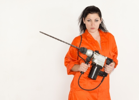 power operated: Competent confident young woman standing holding a cordless masonry power drill in her hands with a long bit attached