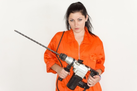 Capable young woman in bright orange overalls holding a large portable drill with a long masonry bit attached photo