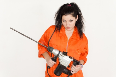 Woman with an attitude standing glowering up at the camera with a large cordless drill with a long masonry bit in her hands photo