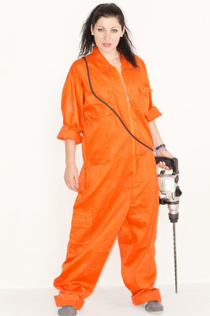 power operated: Confident attractive young woman dressed in bright orange overalls standing holding a large cordless drill at her side