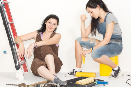 Two happy women taking a break from decorating or renovating a house sitting on the floor surrounded by their painting equipment photo