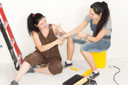 Two female friends or sisters sitting at the foot of a stepladder with their painting equipment congratulating each other and giving a thumbs up at the outcome of their renovation project photo