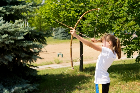 idealism: Girl practising outdoors with a arch and arrow