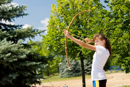 idealism: Girl is taking aim with bow and arrow Stock Photo