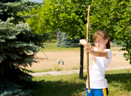 idealism: Little girl is practicing the sport with bow and arrow Stock Photo