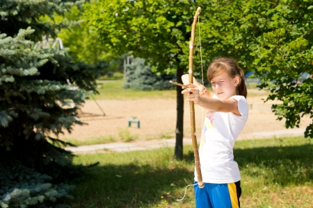 idealism: Girl is practicing the sport of archery outdoors