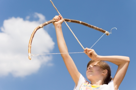 idealism: Girl is aiming her arrow for the clouds