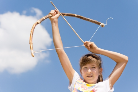 idealism: Girl with her bow and arrow aiming at the sky Stock Photo