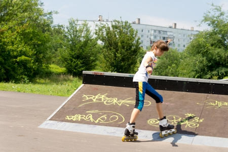 poised: Teenage girl roller skating in a park mounting a cement ramp covered in graffiti